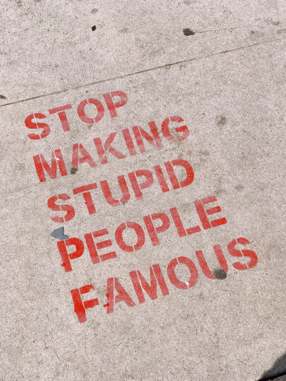 stop making stupid people famous signage