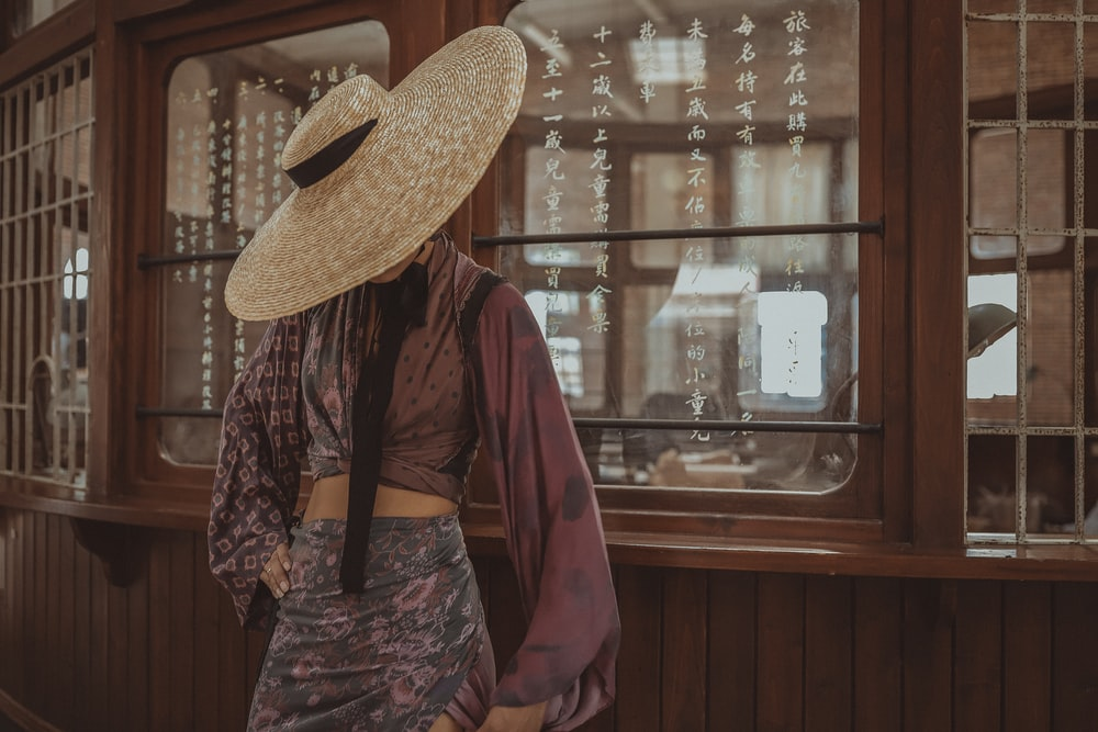 person wearing straw hat standing in front of glass window