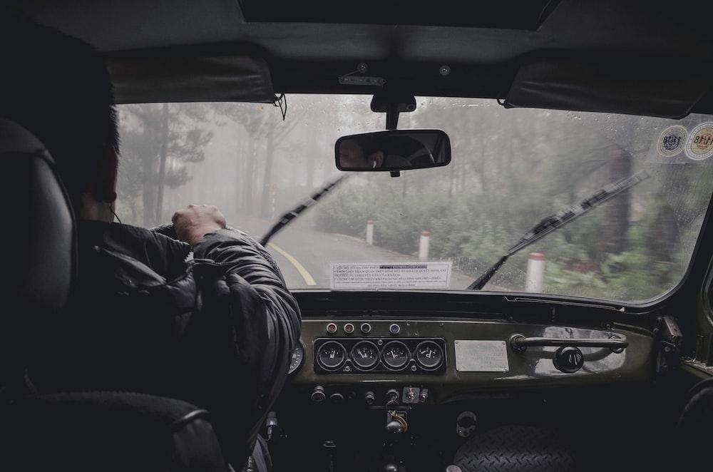 man driving car during rainy daytime