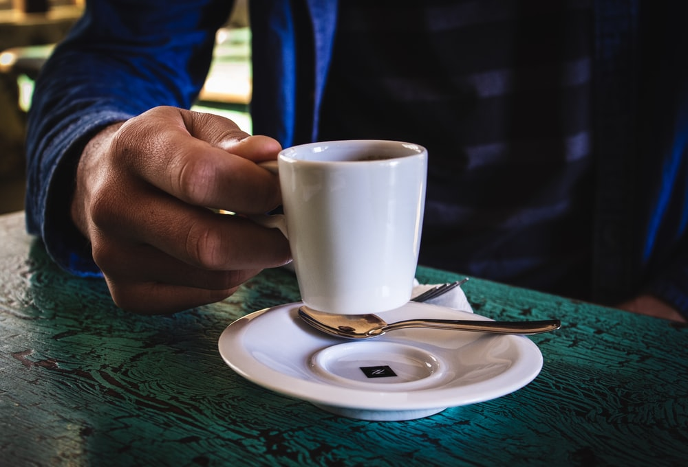 person holding white ceramic mug on saucer
