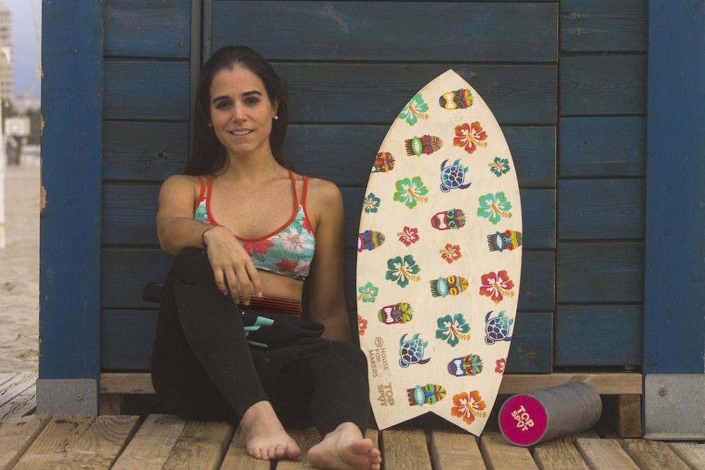 woman sitting on blue surface near skimboard