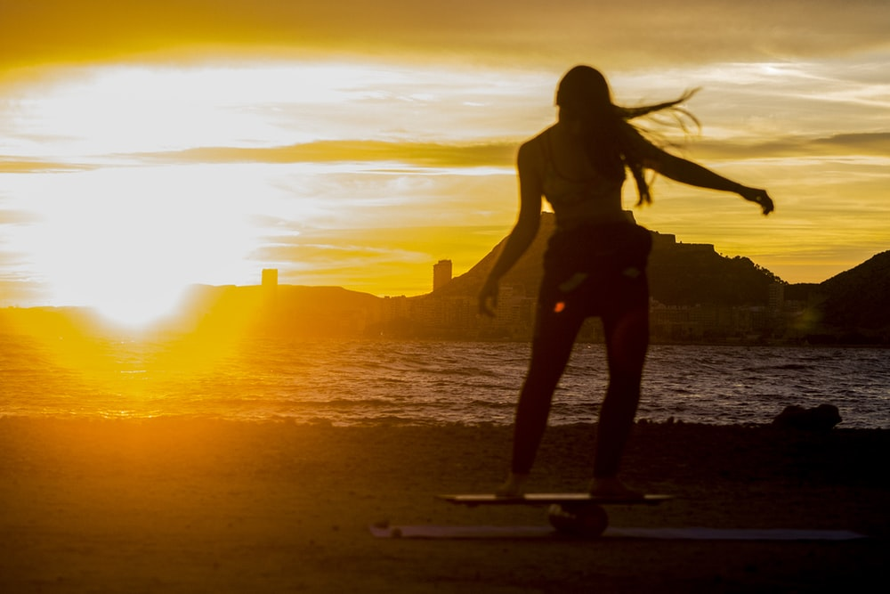 silhouette of woman standing at sunset