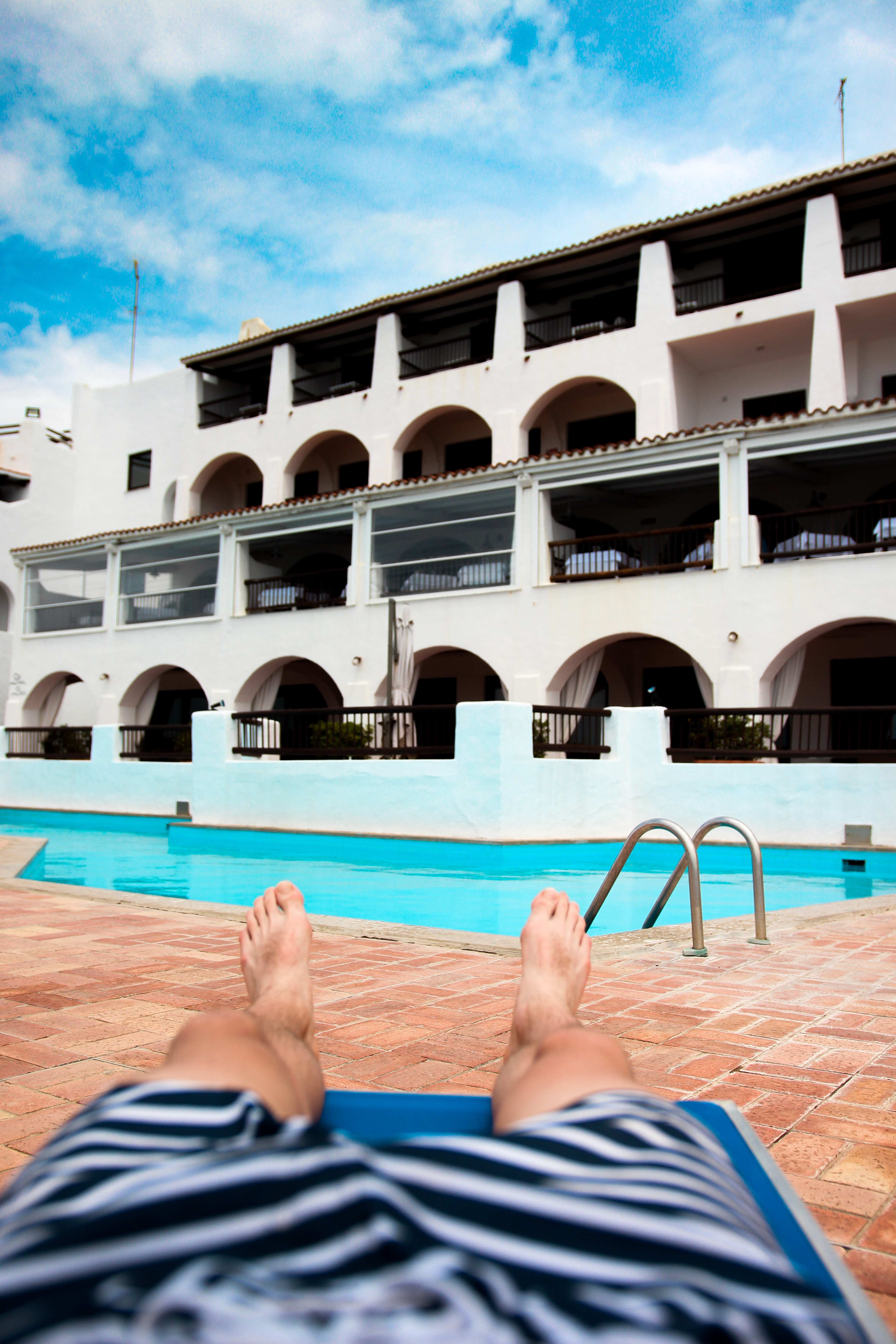 person lying on outdoor lounge chair near swimming pool