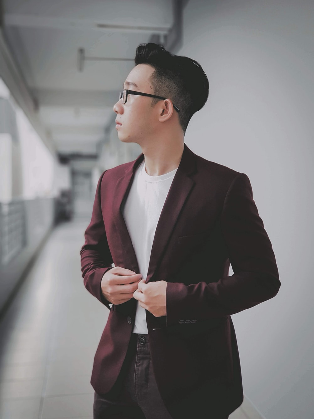 man buttoning his maroon formal suit jacket