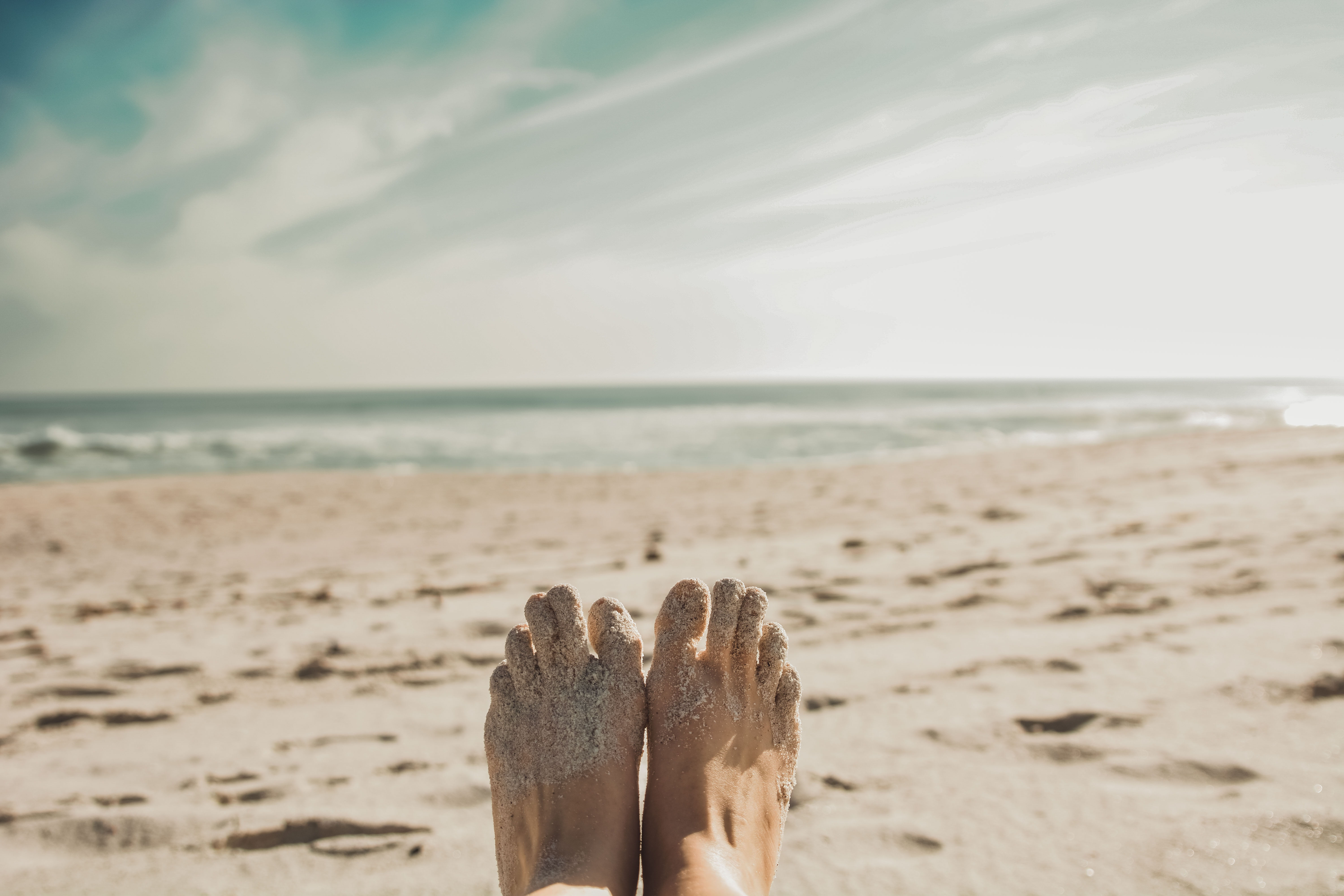 person's feet covered with sand