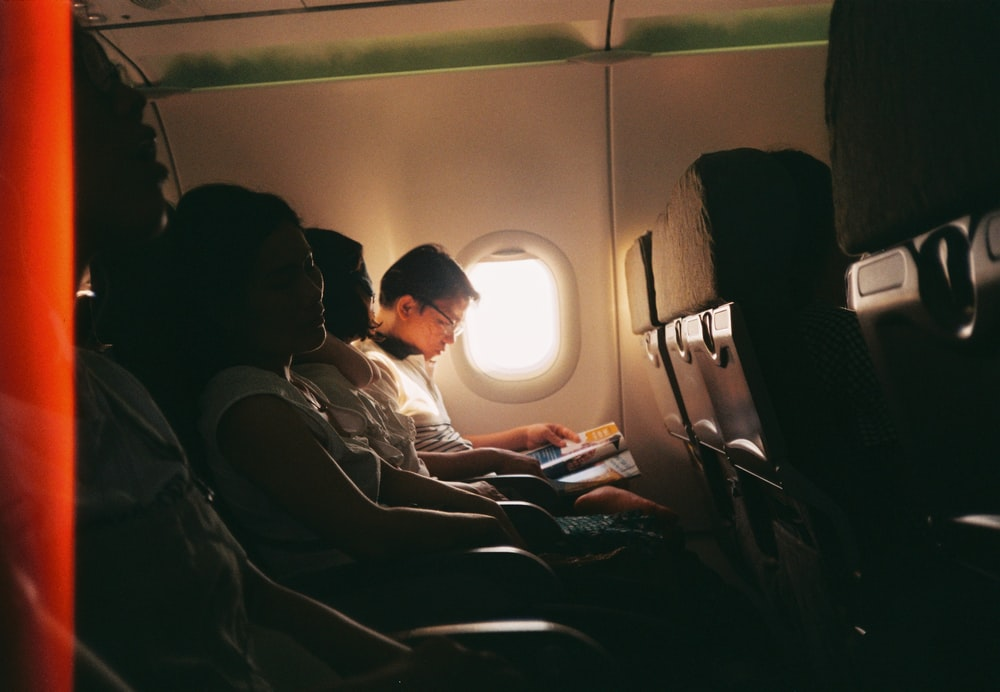 airplane passenger reading book beside the window