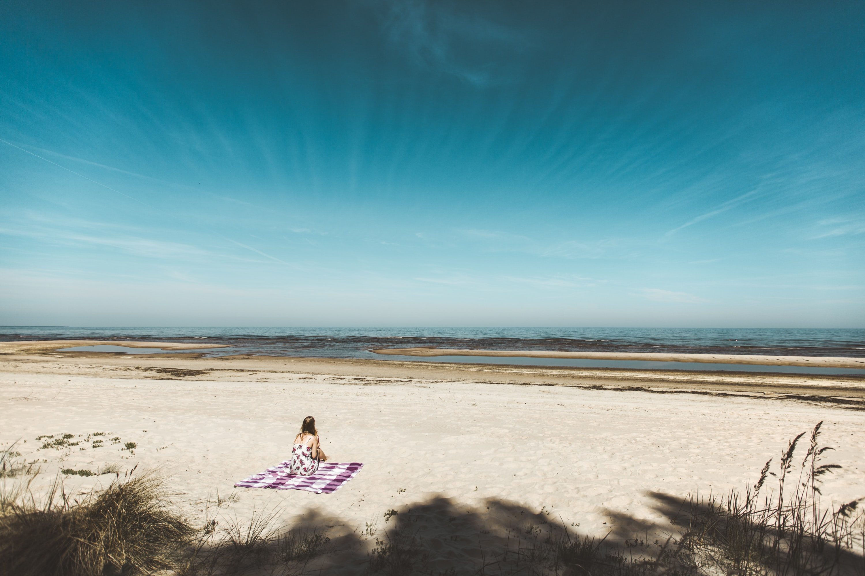 woman sitting on mat placed on gray sand during daytime