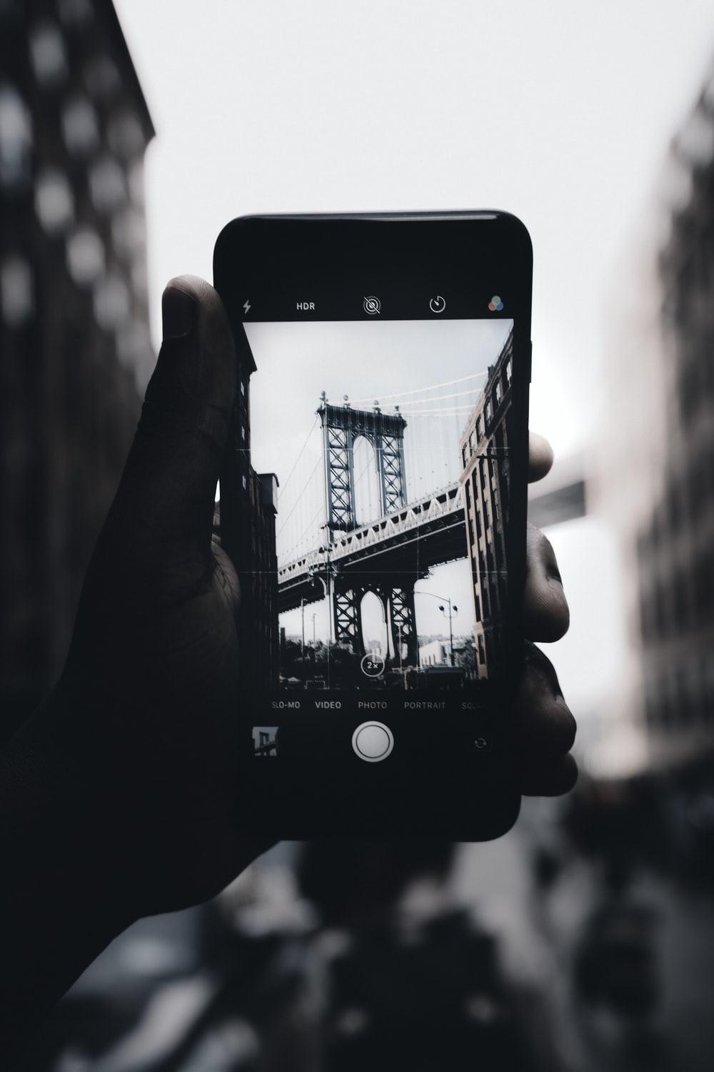 grayscale photography of person holding iPhone capturing bridge