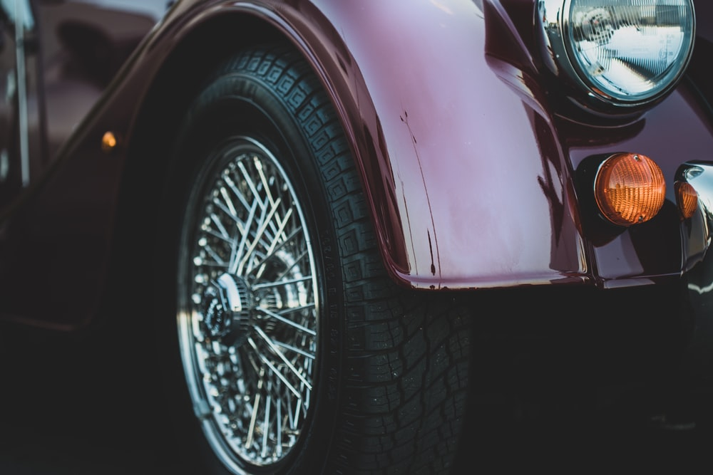 closeup photography of silver-colored vehicle wheel and tire