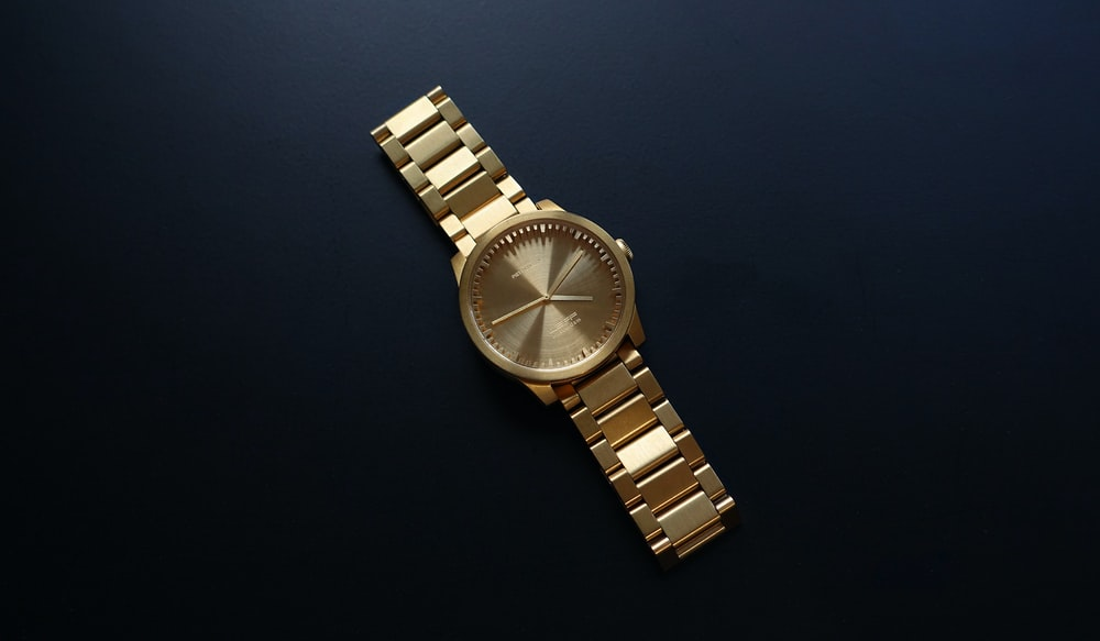 round gold-colored analog watch on black surfac e