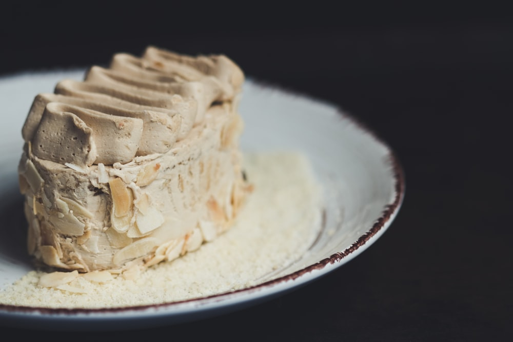 beige icing-covered cake on plate