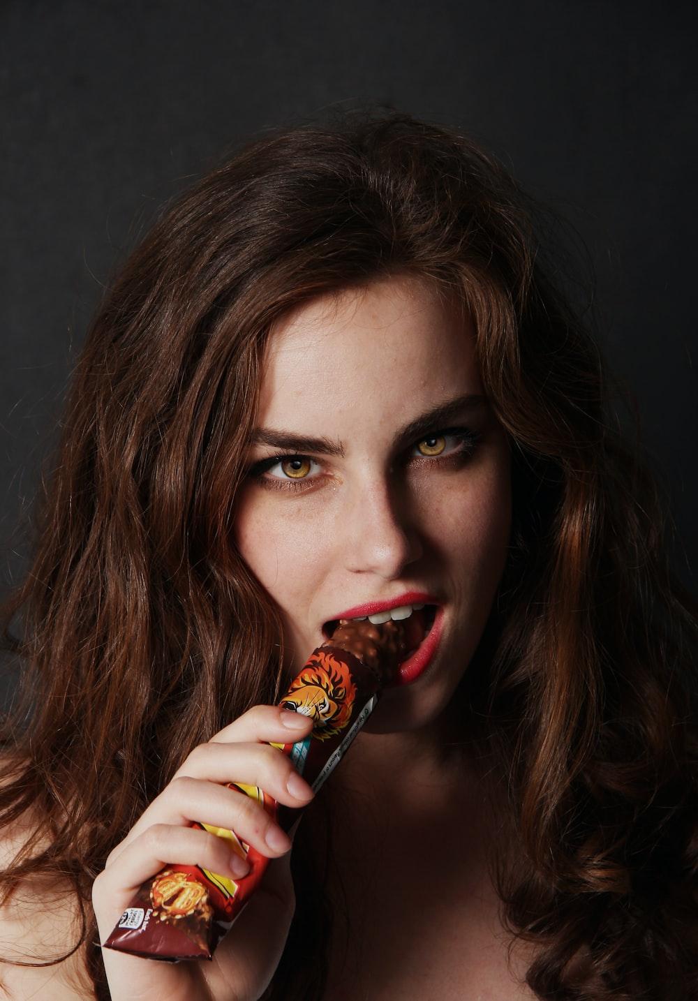 woman biting on chocolate bar