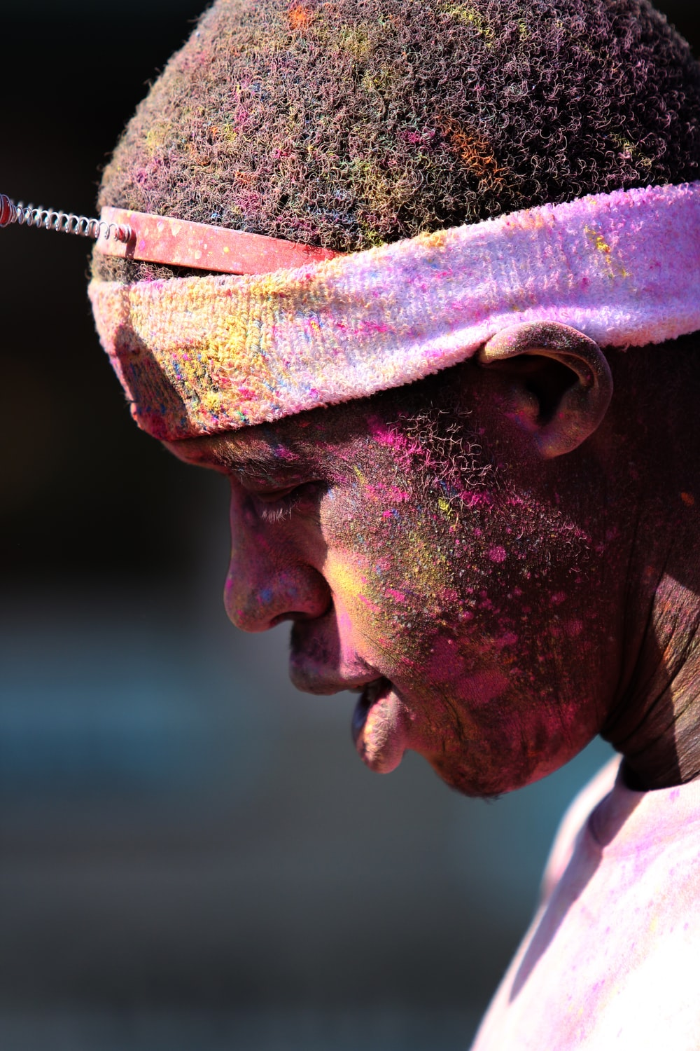 man with pink paint splattered hair and face