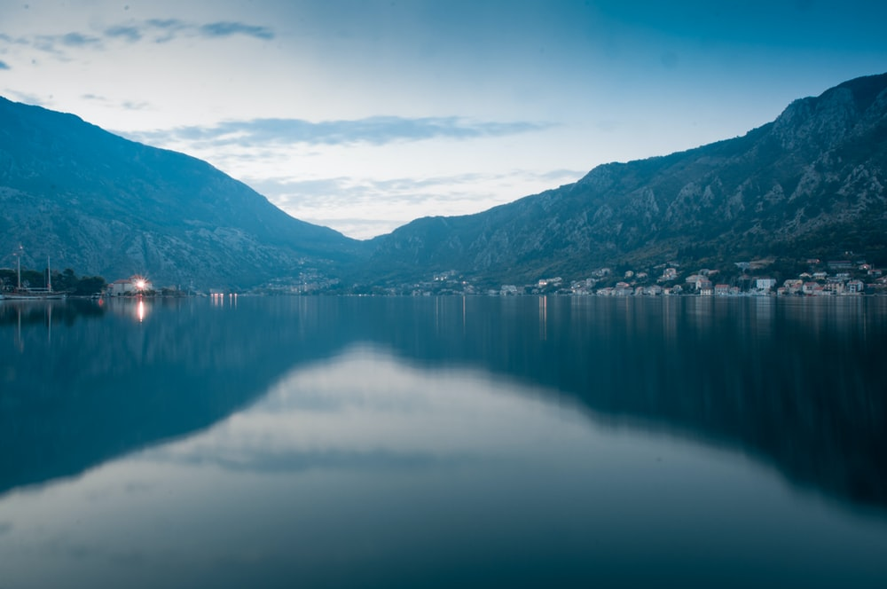 landscape photography of body of water surrounded by hills