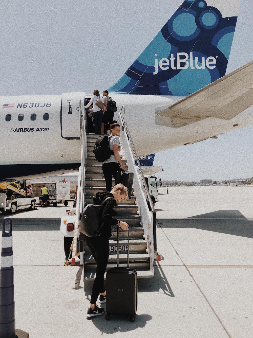 people walking on plane stair during daytime