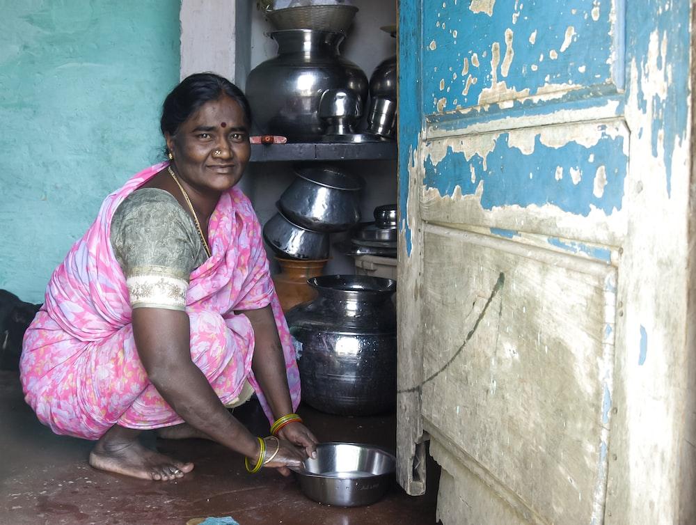 woman kneels on floor holding stainless steel bowl