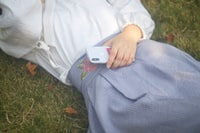 woman lying on grass while holding silver iPhone X