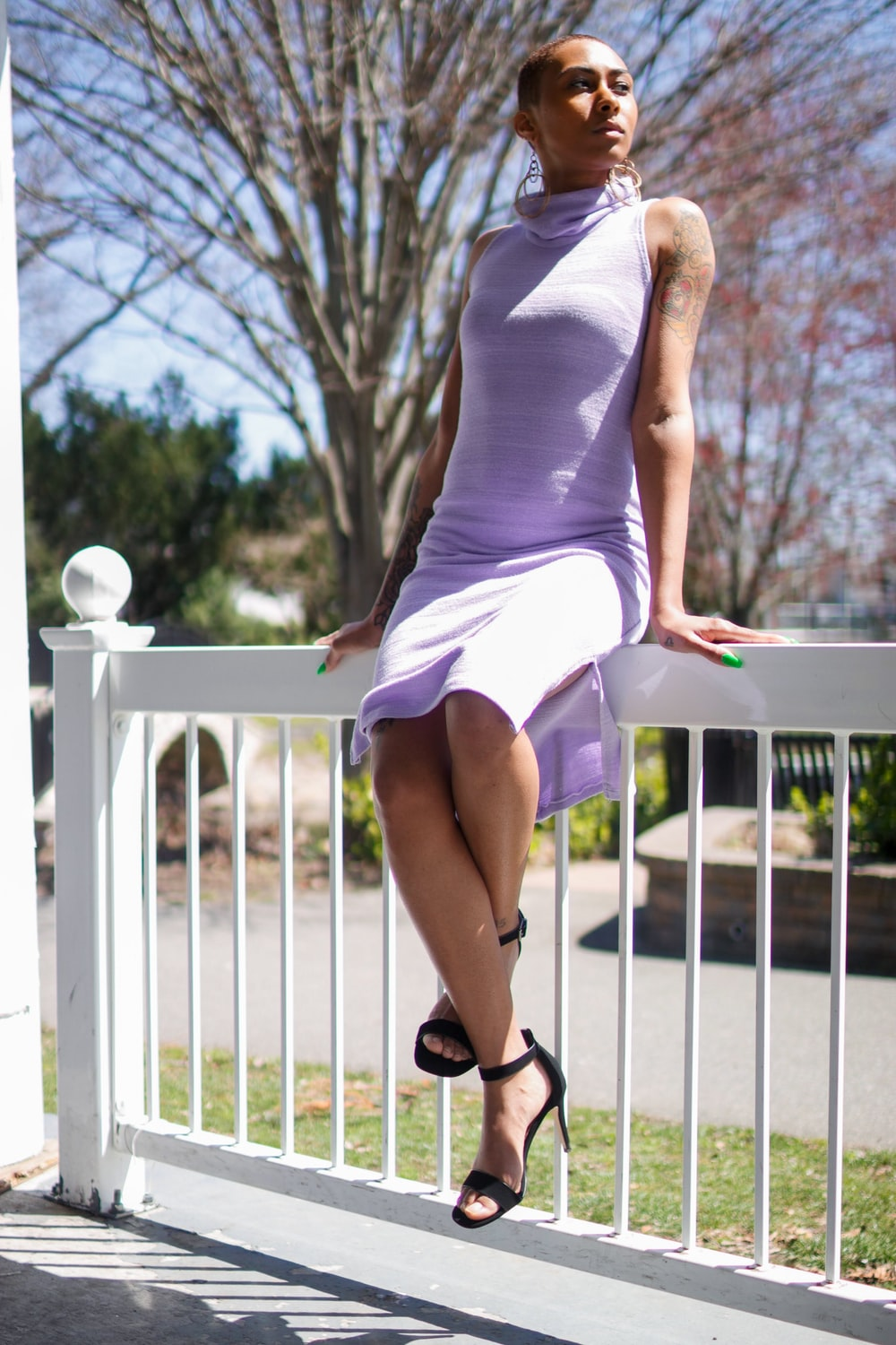 woman in pink dress sits on porch balustrade