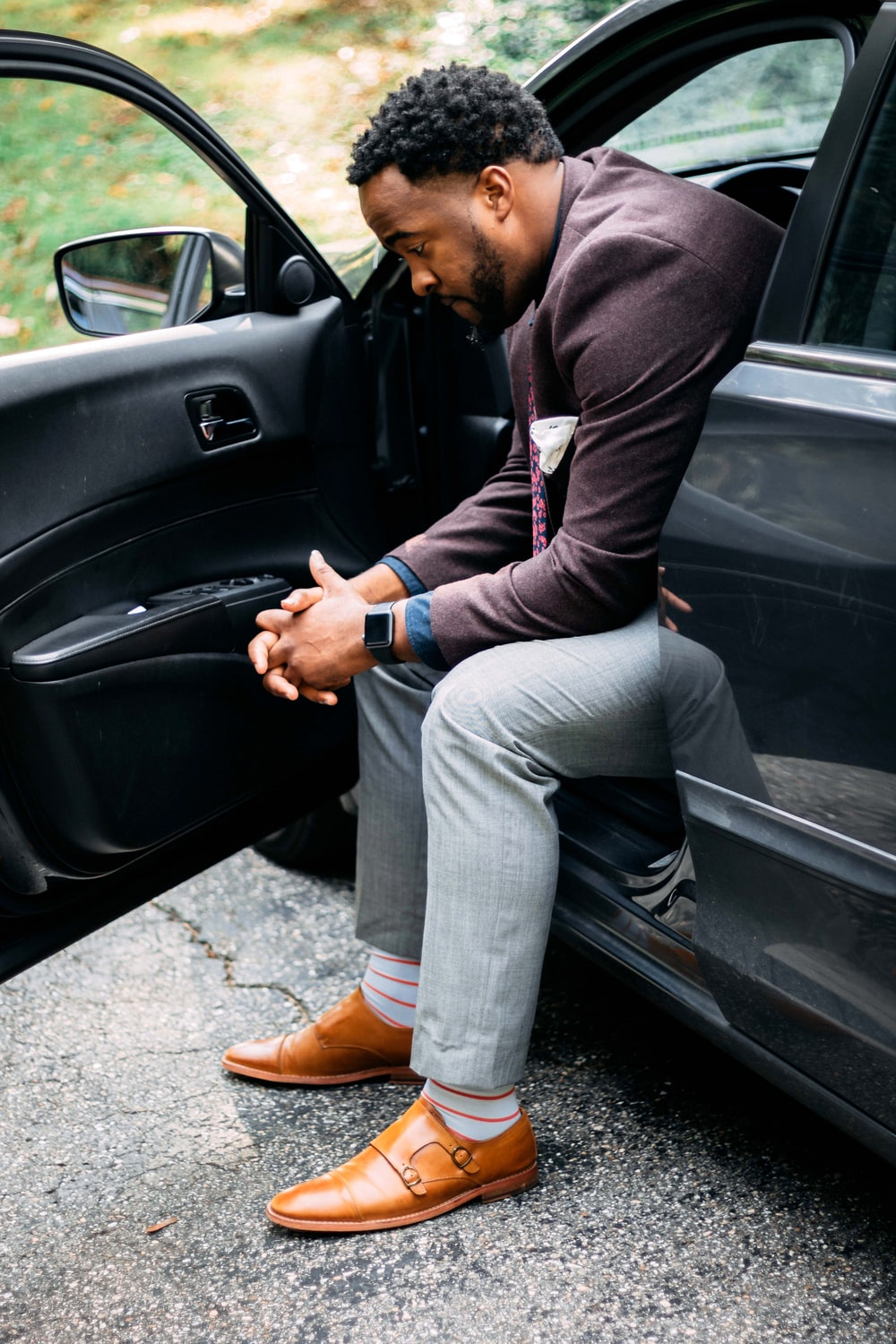 Man alone sitting outside his car