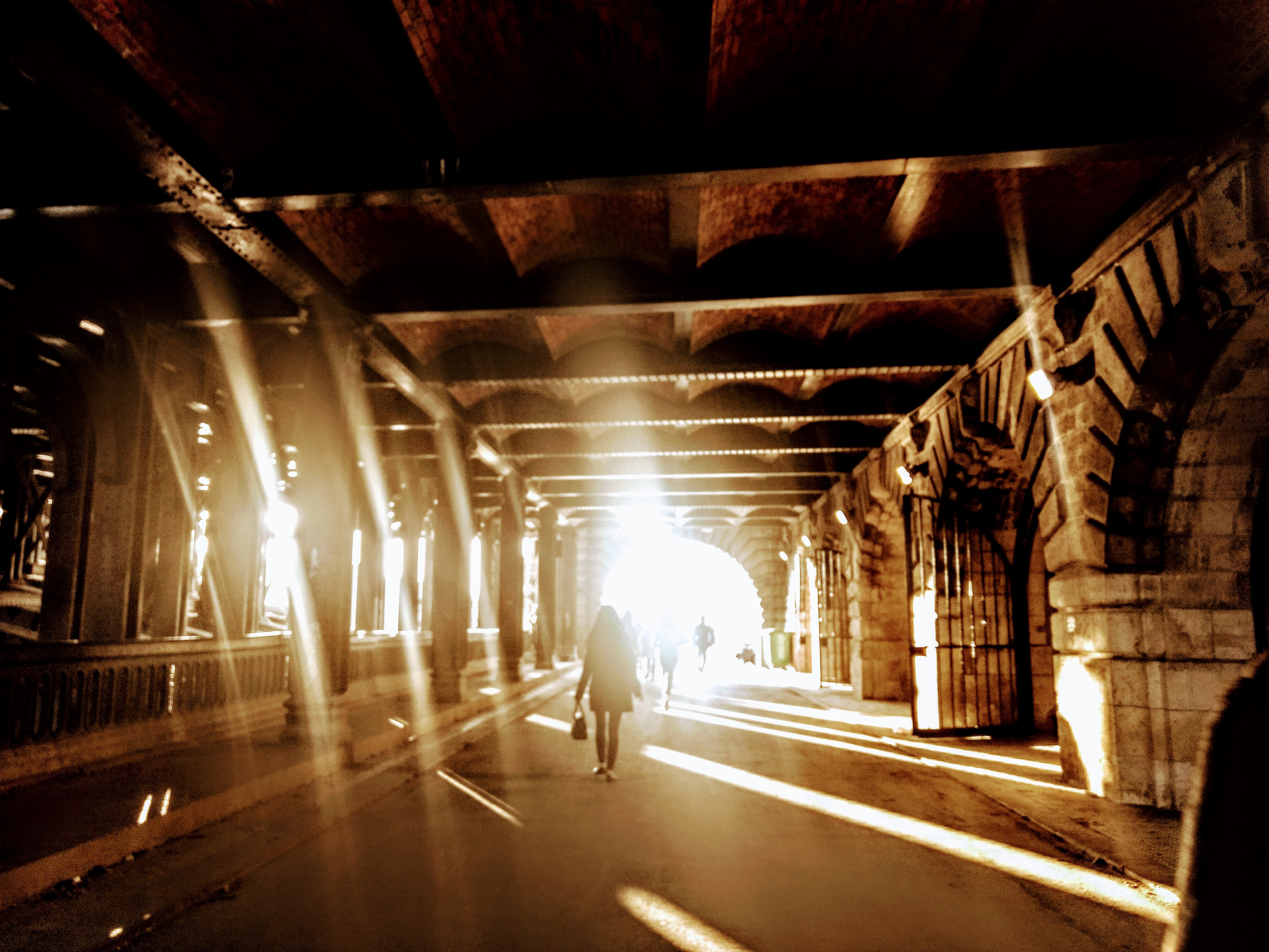 person walking in tunnel during daytime