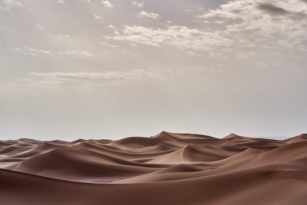 brown desert under white clouds