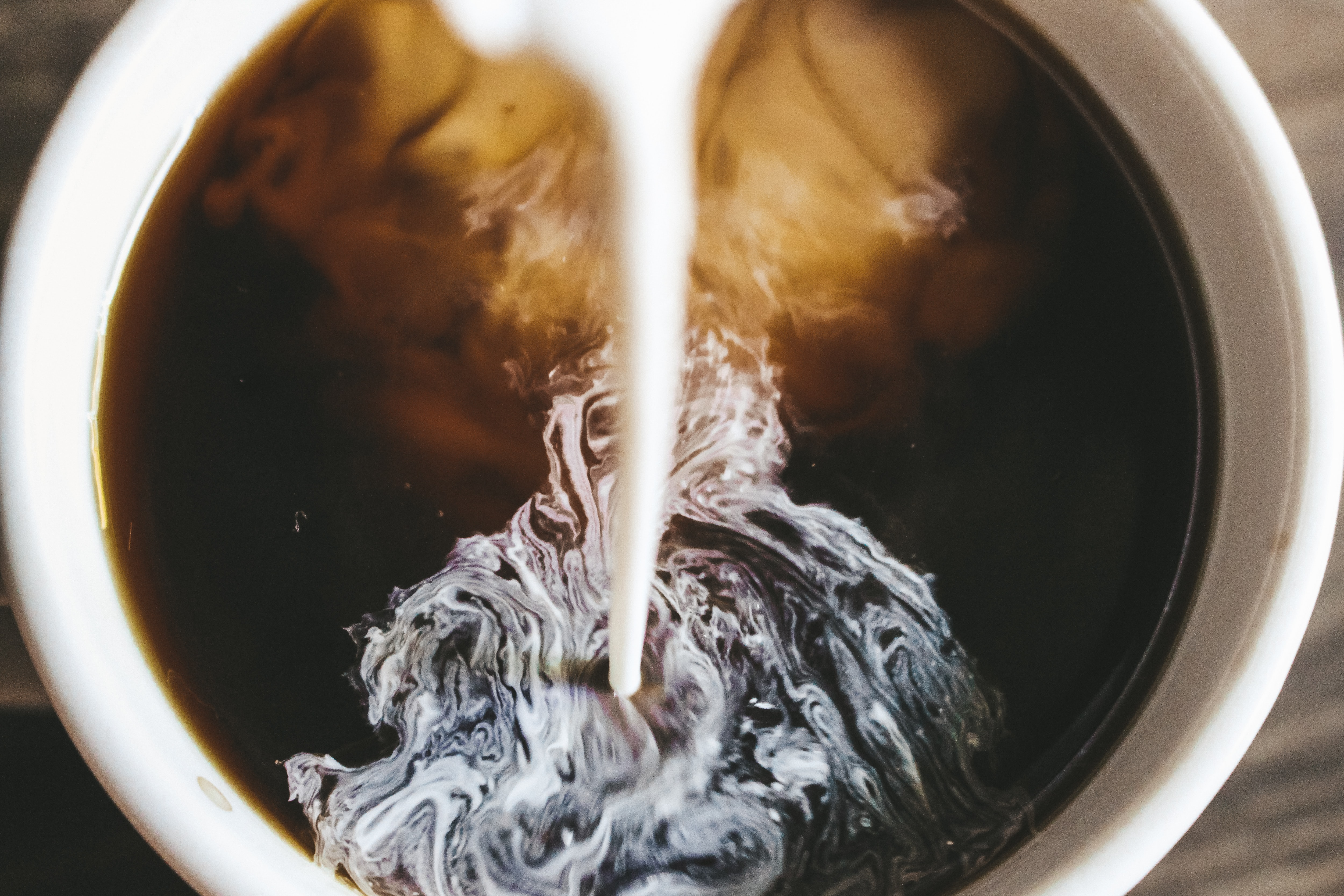 milk pouring into a coffee-filled cup