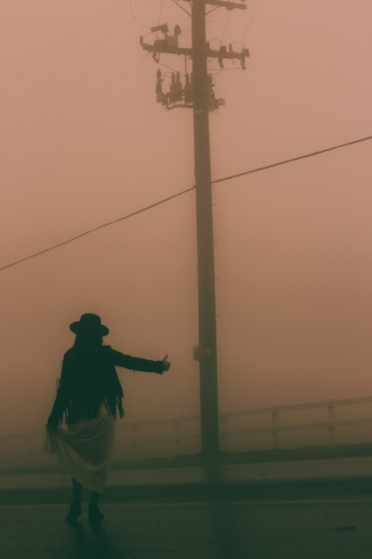 person standing near street post