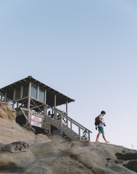 person walking on rock in front of a hut