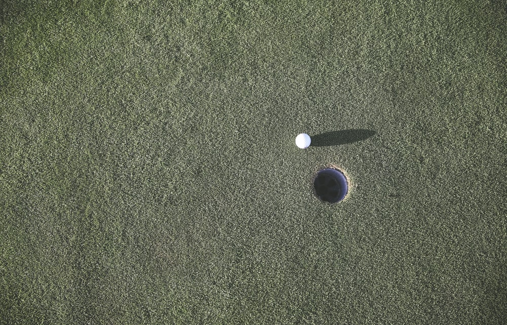 white golf ball near hole
