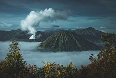 green mountains surrounded by white clouds volcano teams background