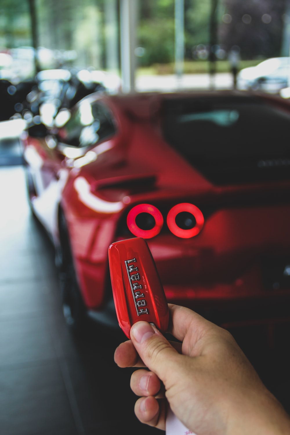 red person with keyfob of red Ferrari supercar