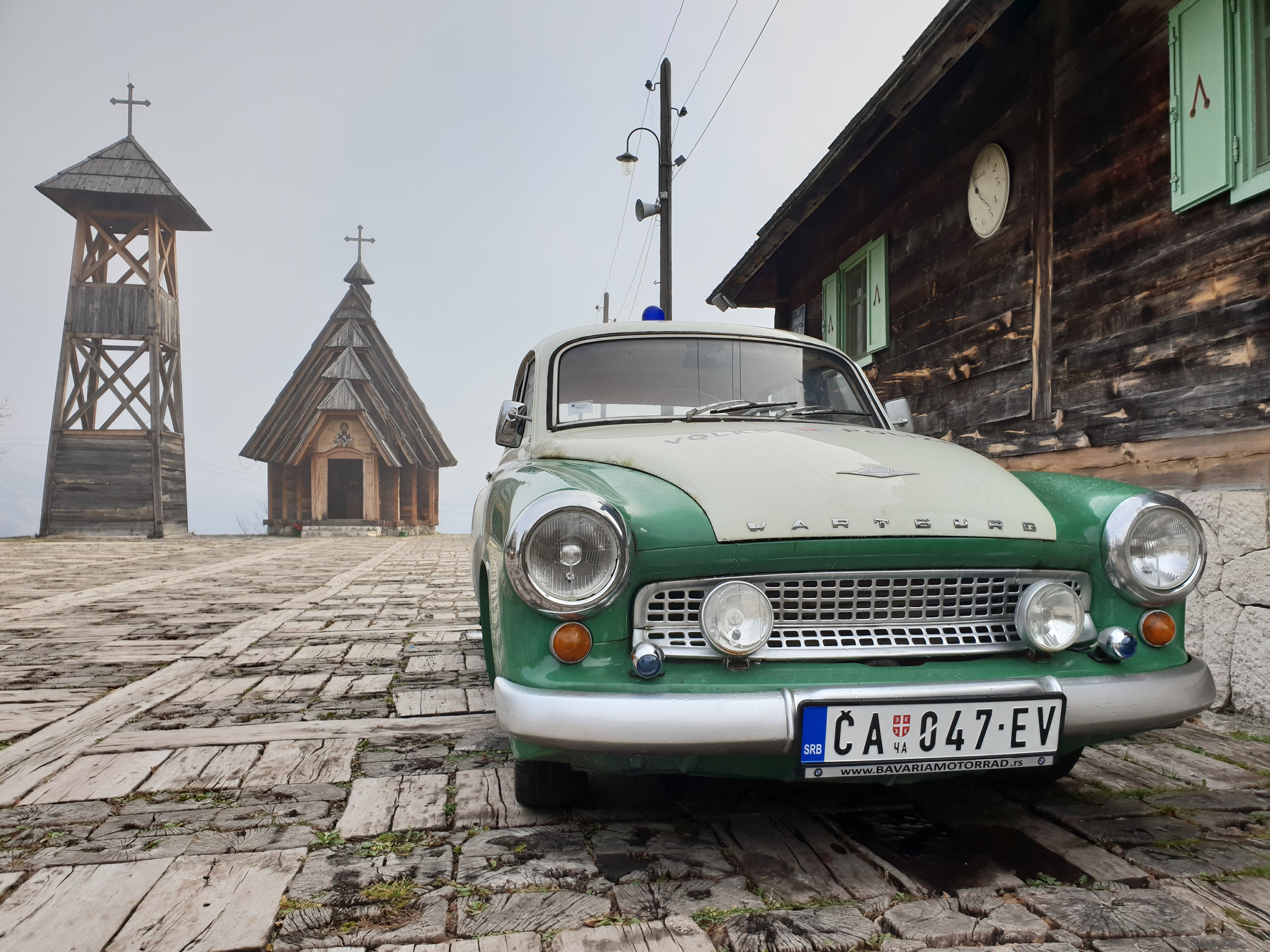green and white vehicle near wooden buildings