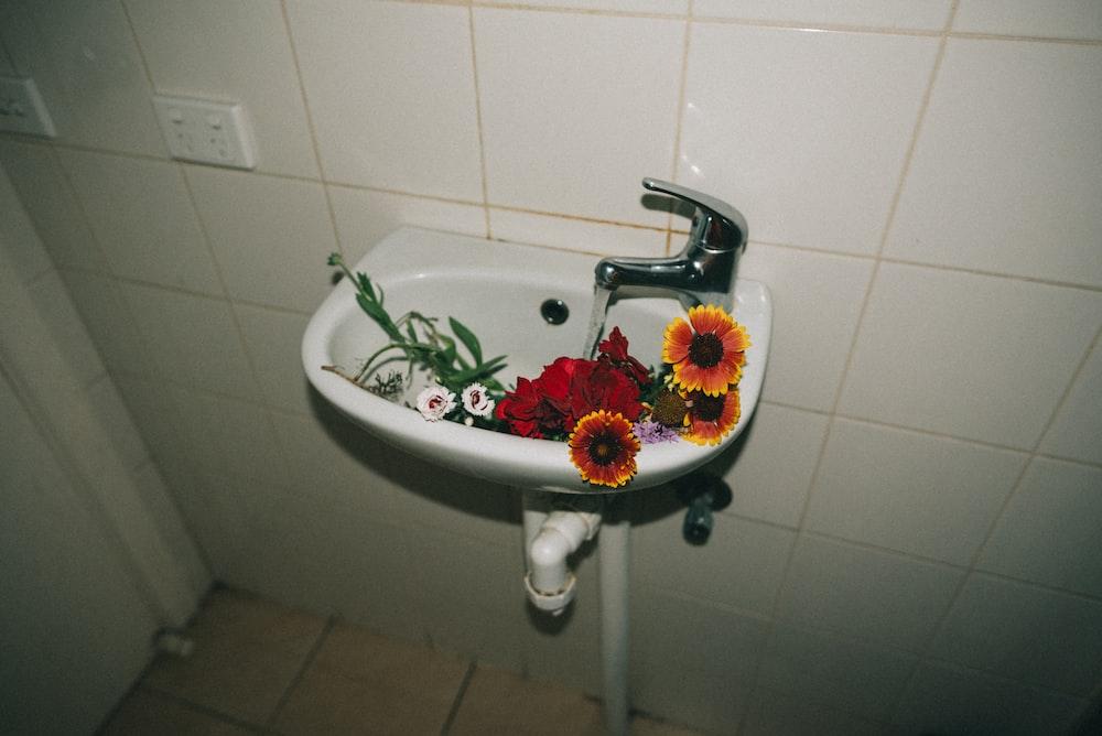 variety of flowers in white ceramic pedestal sink