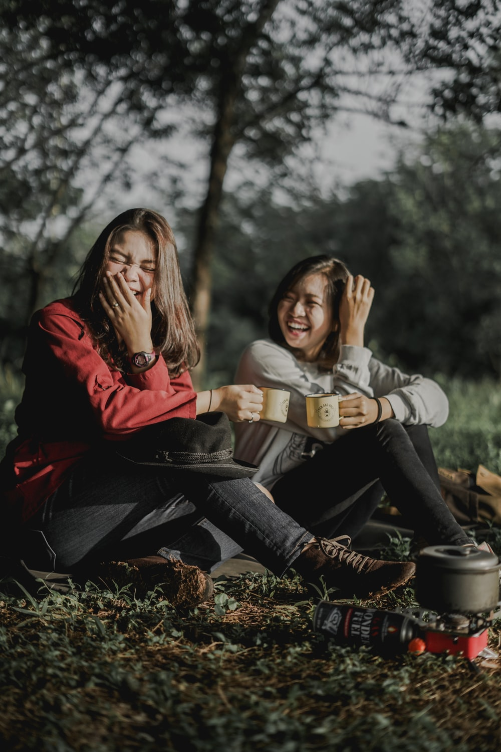 two women holding cups laughing at each other