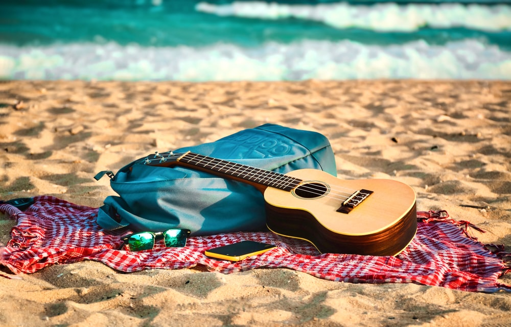 natural finish acoustic guitar near yellow tablet and sunglasses on red blanket placed on seashore