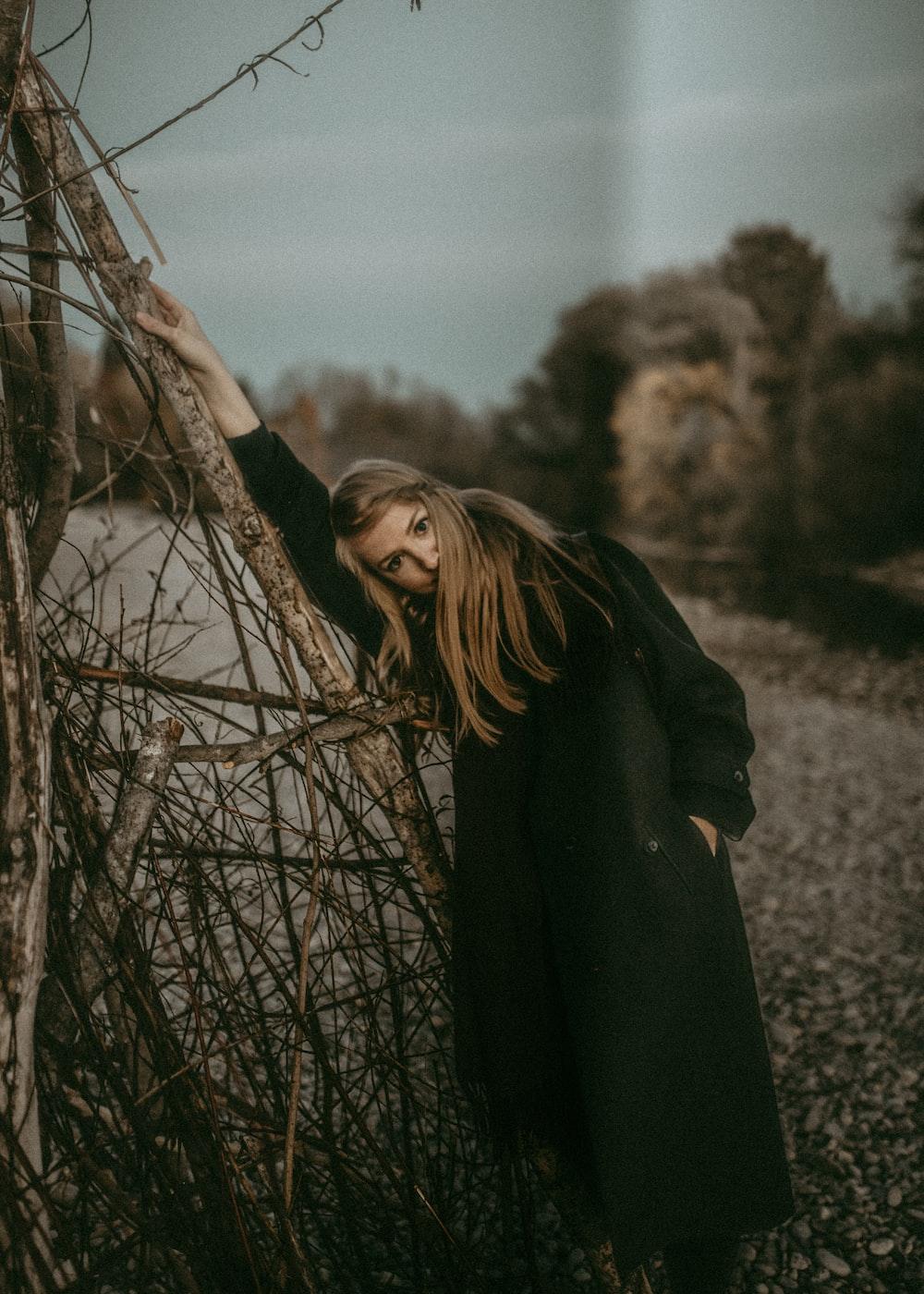 woman standing beside twigs