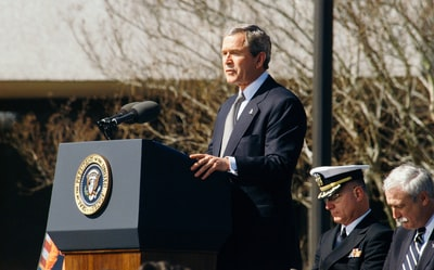 george w. bush standing on lectern during daytime republican teams background