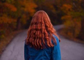 woman in denim jacket walking on empty road