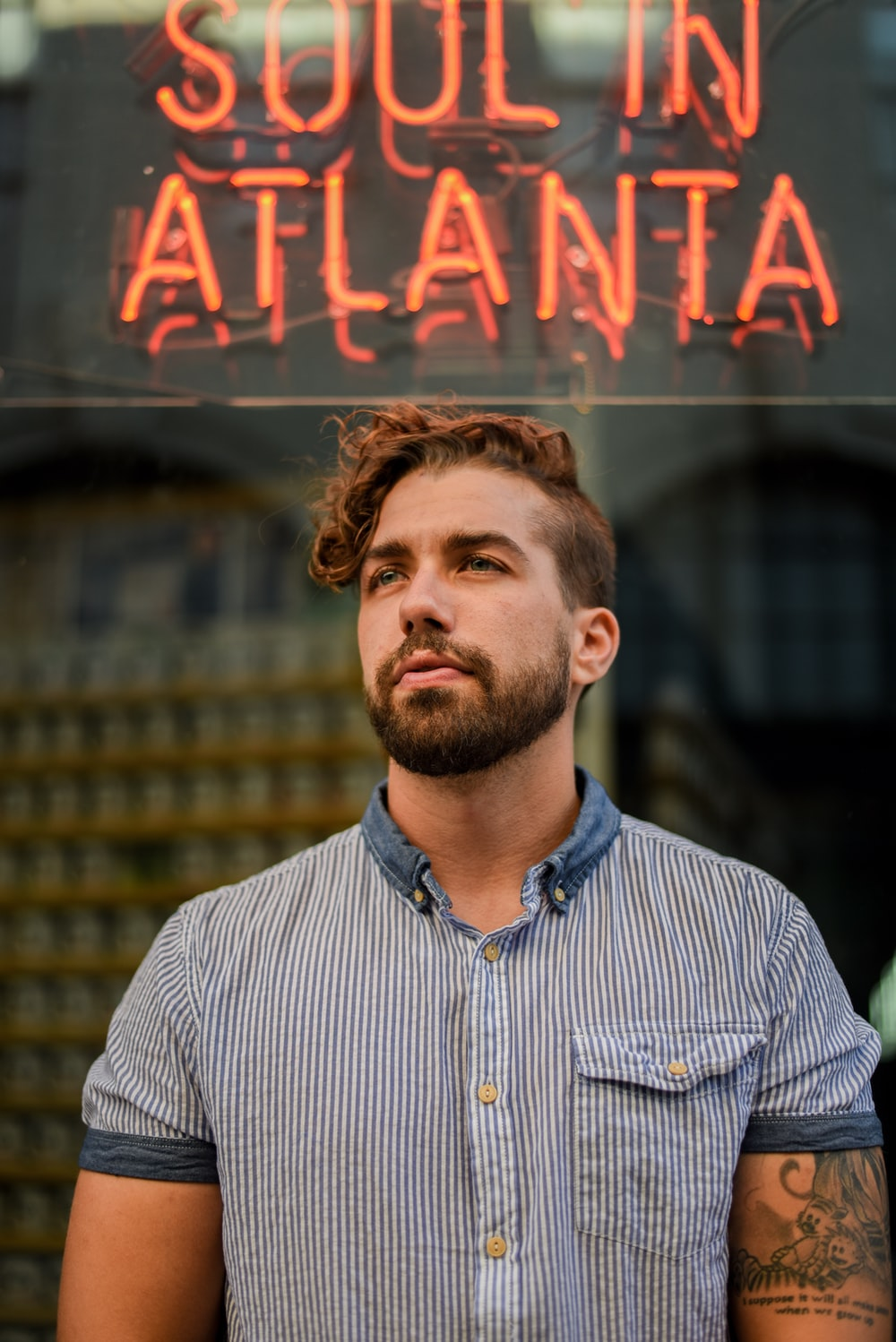 man standing near red neon signage