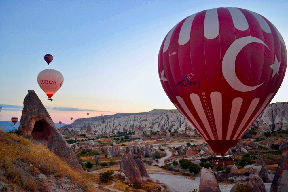 hot air balloons above mountains