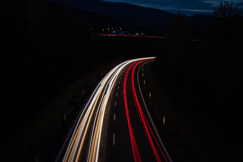 time lapse photo of vehicles on road during night time