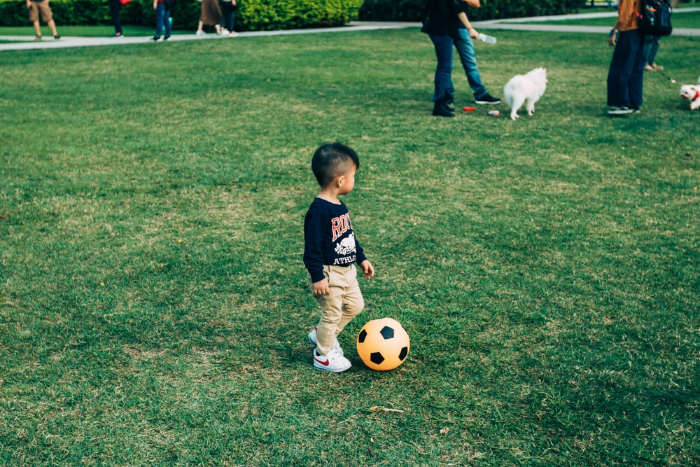 boy playing soccer on grass field