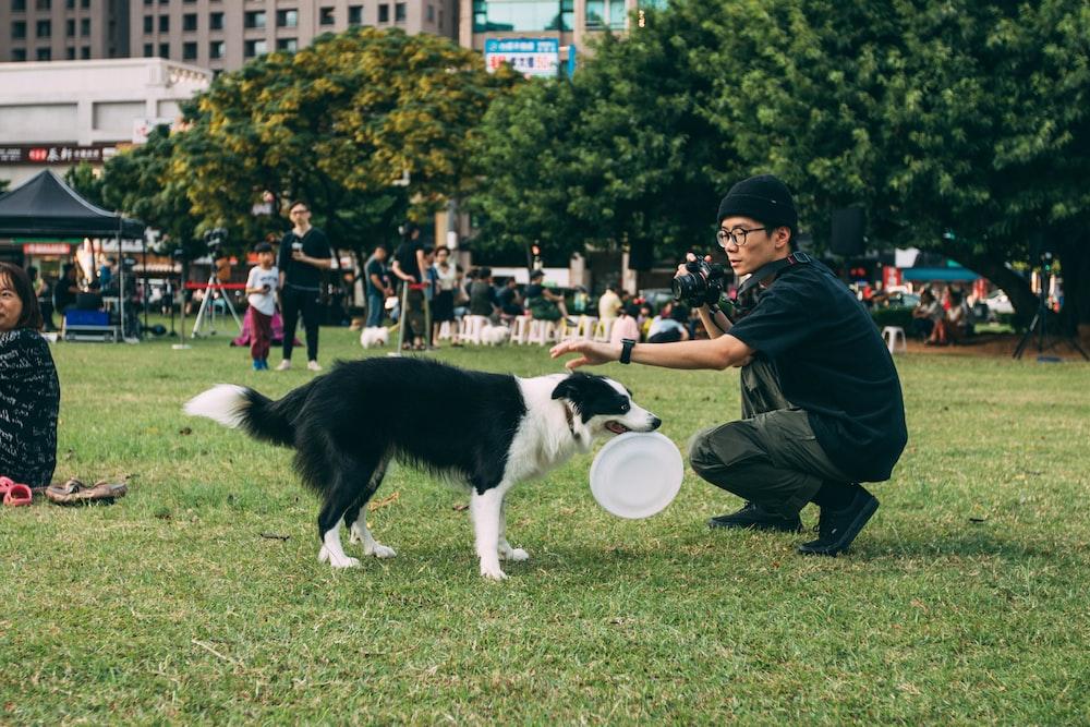 man holding black and white dog