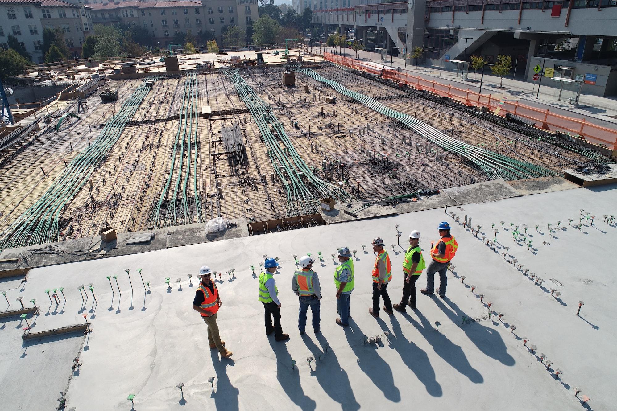 Sete trabalhadores e gestores da indústria da construção civil olhando para uma obra.
