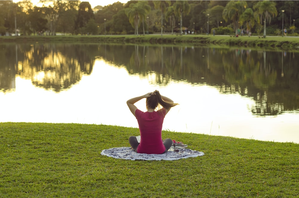 woman sitting on mat in front of body of water