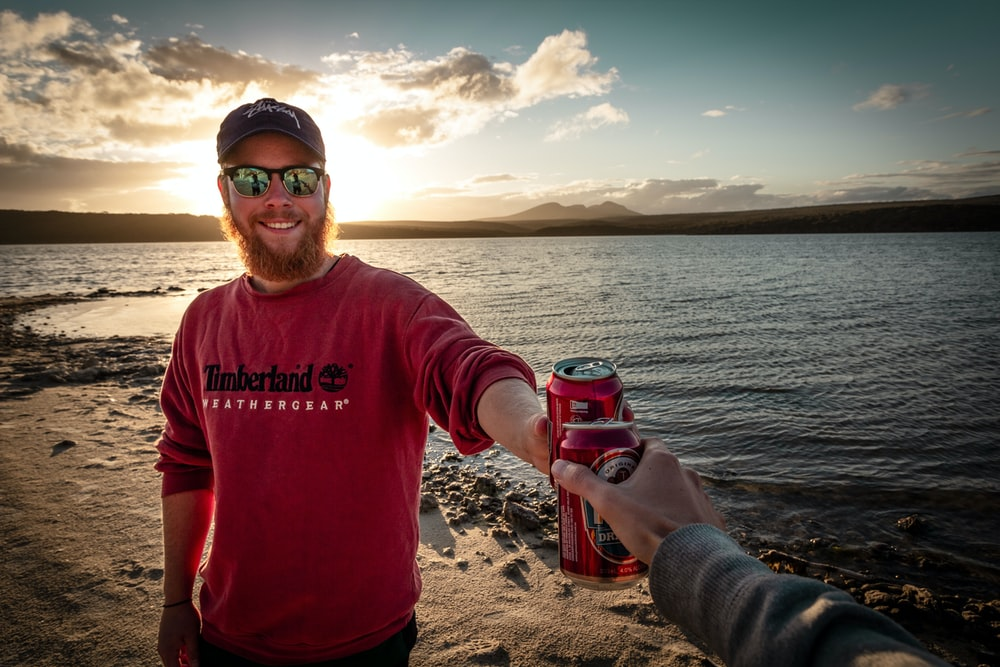 man in red sweater toasting red beverage can near body of water during daytime