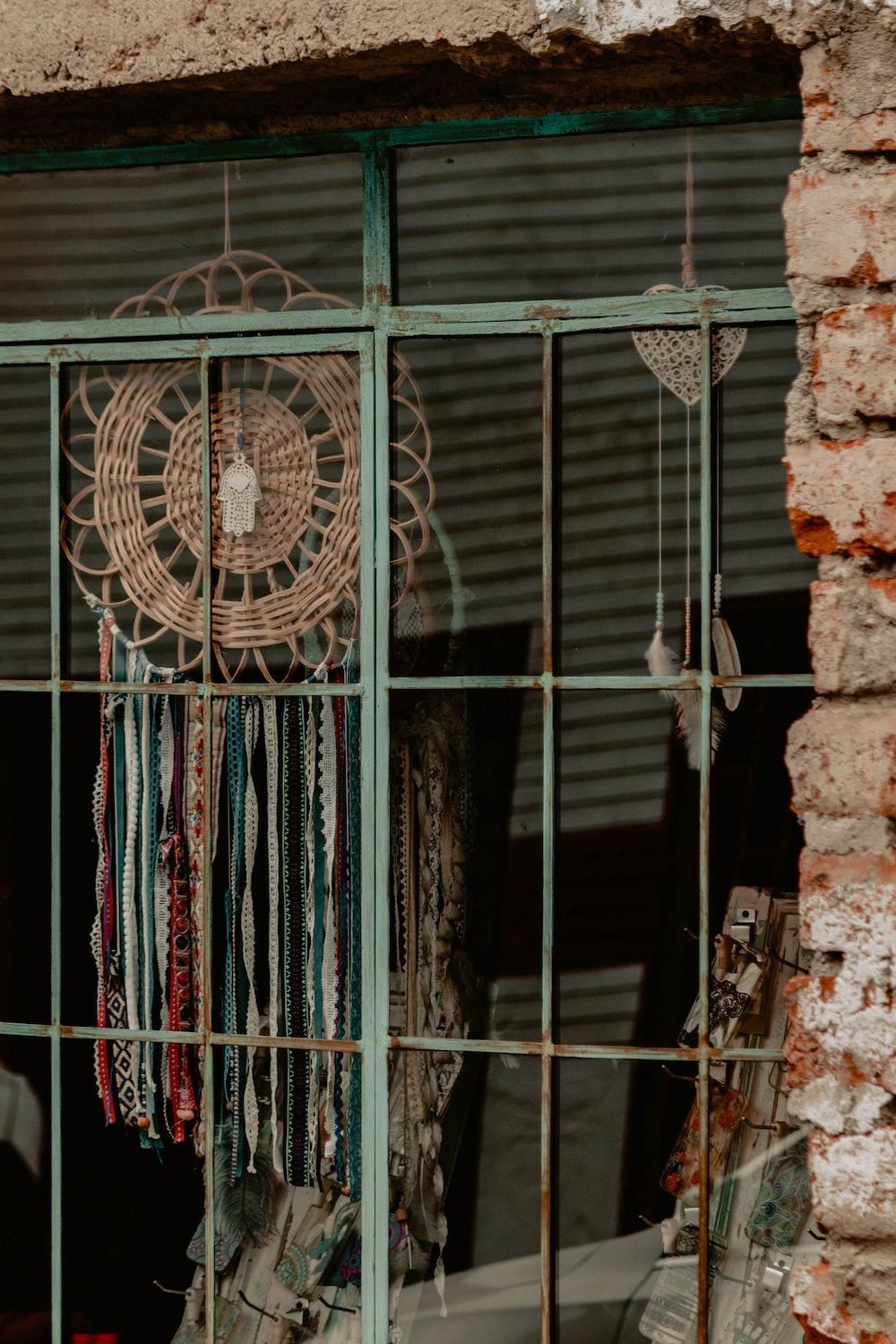 brown and teal dreamcatcher beside window
