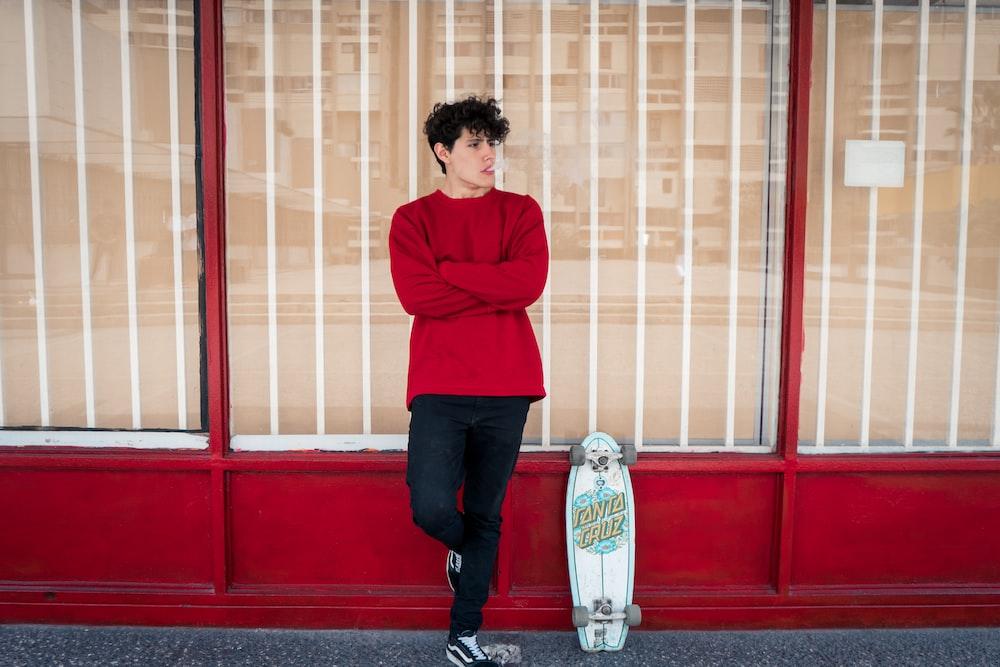 man leaning on glass wall beside leaning skateboard
