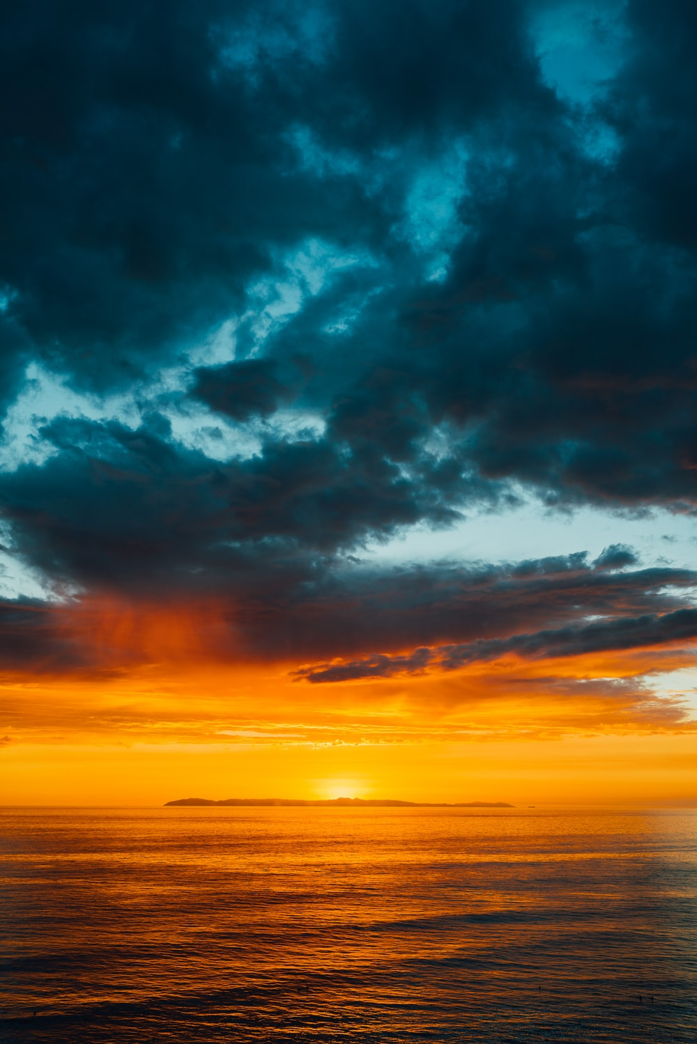green and black clouds partly covering orange sky over sea at sunset