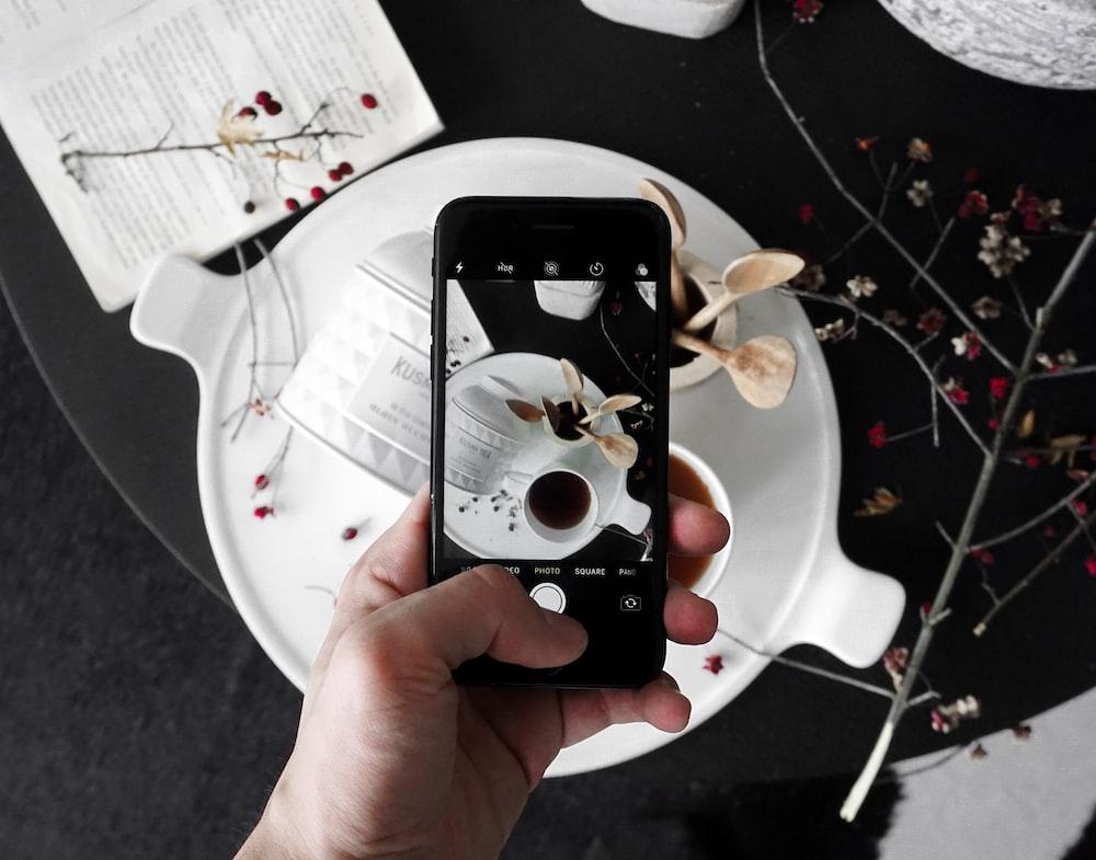 black iPhone 7 displaying teacup with orange liquid